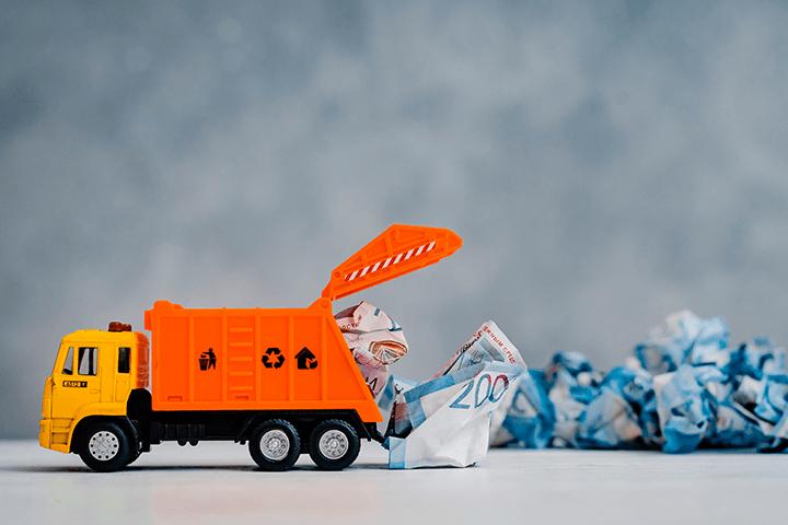 Caminhão de lixo de brinquedo carregando dinheiro e reserva de emergência onde investir