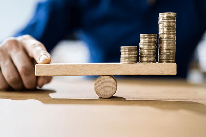 Moedas em uma balança de madeira representando investimentos atrelados a inflação