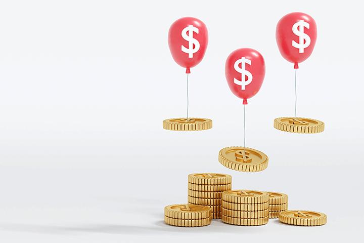 Moedas flutuando com balão com cifrão representando inflação e investimentos atrelados a inflação