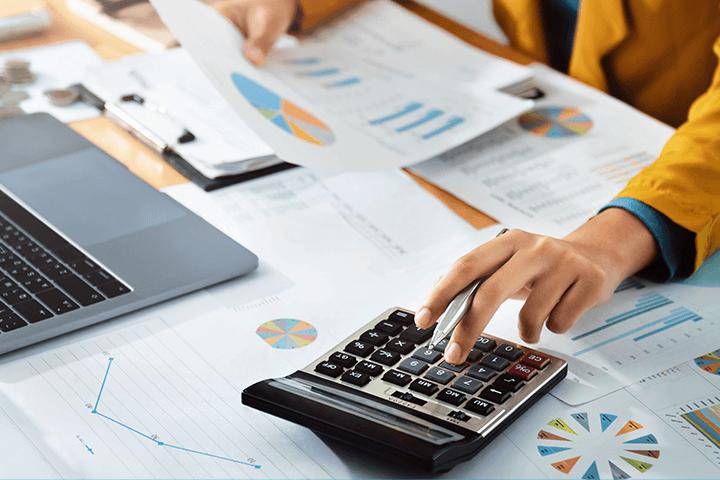 Mulher com calculadora fazendo conta da rentabilidade real dos investimentos