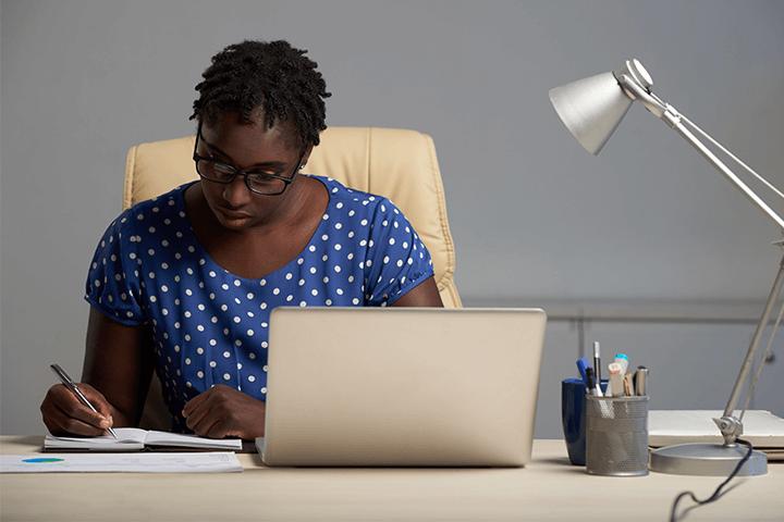 Mulher negra sentada à mesa escrevendo em um caderno com um notebook próximo de si exercendo a profissão de planejador financeiro