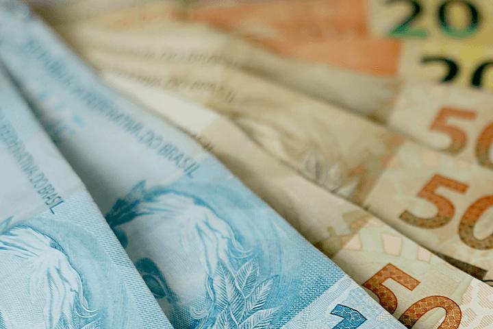 A imagem mostra notas de cem, cinquenta e vinte reais dispostas umas sobre as outras. Selic e inflação.