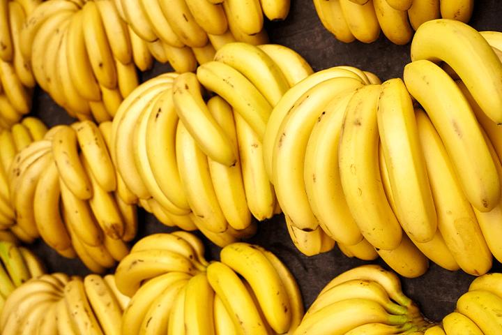 Cachos de bananas dispostos numa tábua de madeira. Selic e inflação.