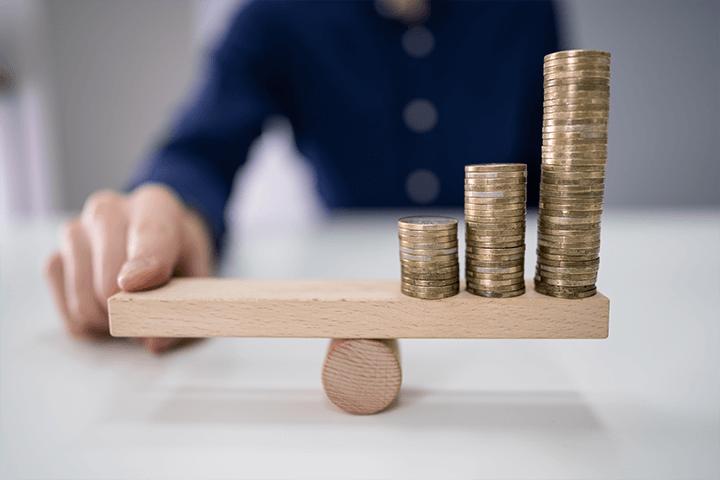Homem equilibrando uma gangorra feita com blocos de montar de madeira. De um lado está a mão dele, do outro estão três pilhas de moedas. Selic e inflação.