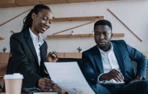 Mulher exercendo a profissão de planejador financeiro. Ela está sorrindo e mostrando uma folha de papel para seu cliente e segura uma caneta. Ambos são negros e estão vestidos com roupas sociais em um escritório.